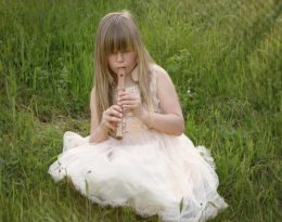 Child playing the recorder in a field