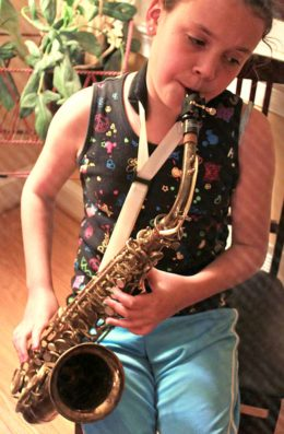 girl playing vintage king zephyr saxophone